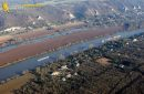 Barges and transport boats on the Seine river seen from the sky at Haute-Isle en Vexin