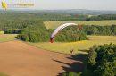 Paramoteur en vol au dessus des champs de l'yonne, en région Bourgogne-Franche-Conté,France